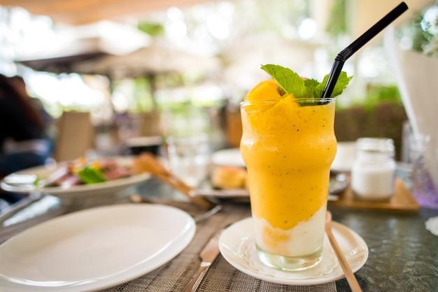 Délicieux smoothie tropical mélangé avec mangue, orange et fruit de la passion