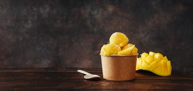Délicieux sorbet végétalien à la mangue dans un gobelet en papier artisanal sur fond sombre