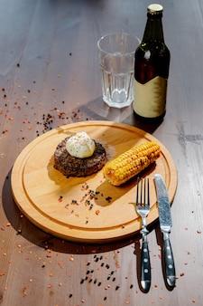 Délicieux steak de boeuf aux épices et herbes sur une planche à découper et une table en ardoise.escalope de viande frite juteuse sur une planche à découper en bois