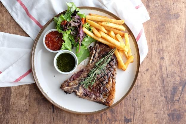 Délicieux steak de bœuf avec frites et sauce chili