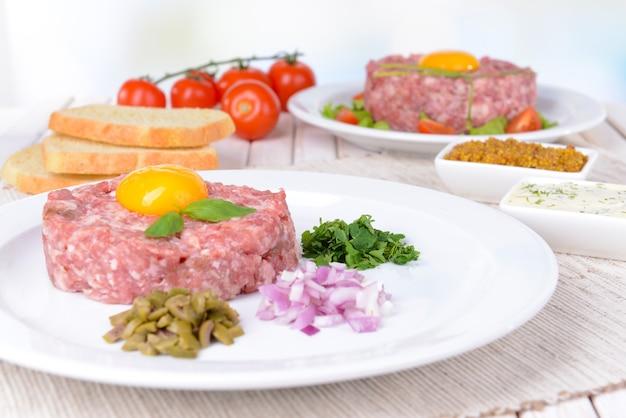 Délicieux steak tartare avec jaune sur plaque sur table close-up