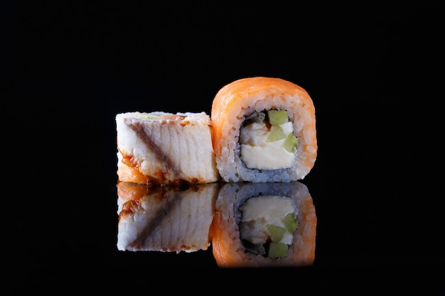 Délicieux sushi rouleau avec du poisson sur un fond noir avec reflet menu et restaurant