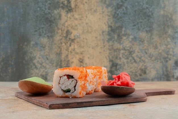 Délicieux sushis au caviar, gingembre et vasabi sur plaque en bois.
