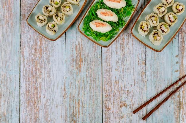 Délicieux sushis et petits pains avec des baguettes pour la fête