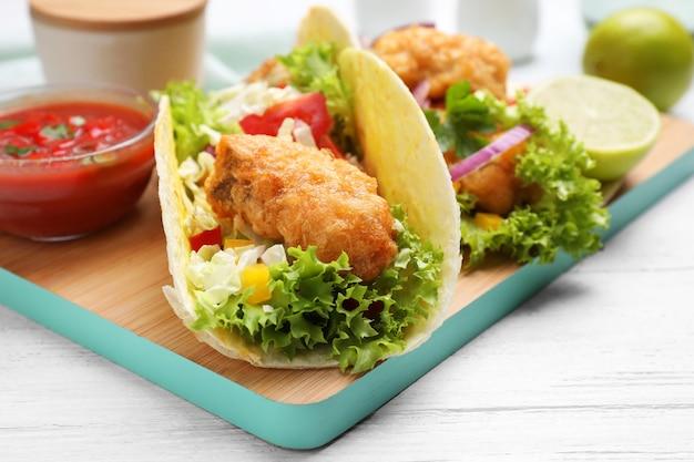 Délicieux tacos au poisson servis sur une table en bois blanc, gros plan