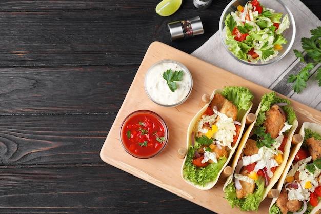 De délicieux tacos au poisson servis sur une table en bois foncé, à plat