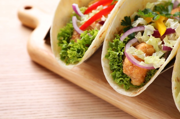 Délicieux tacos au poisson servis sur table en bois, gros plan