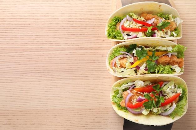 Délicieux tacos au poisson servis sur une table en bois, vue de dessus avec un espace pour le texte