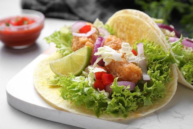 Délicieux tacos au poisson servis sur une table gris clair, gros plan