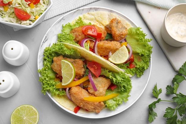 De délicieux tacos au poisson servis sur une table gris clair, à plat