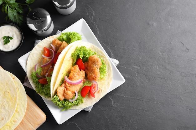 De délicieux tacos au poisson servis sur une table gris foncé, à plat avec un espace pour le texte
