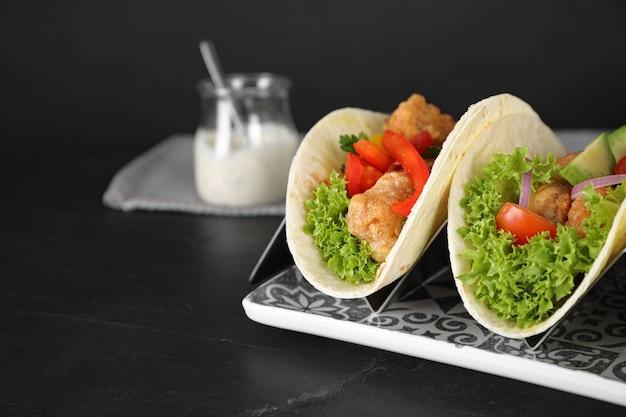 Délicieux tacos au poisson servis sur une table noire, espace pour le texte