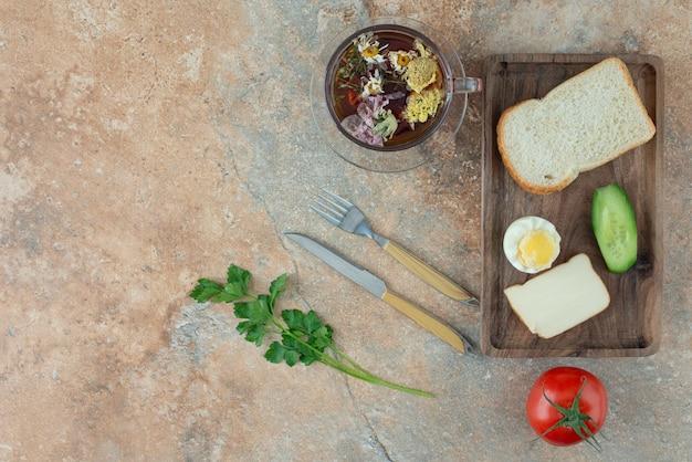 Délicieux thé à la camomille avec tomate et pain.