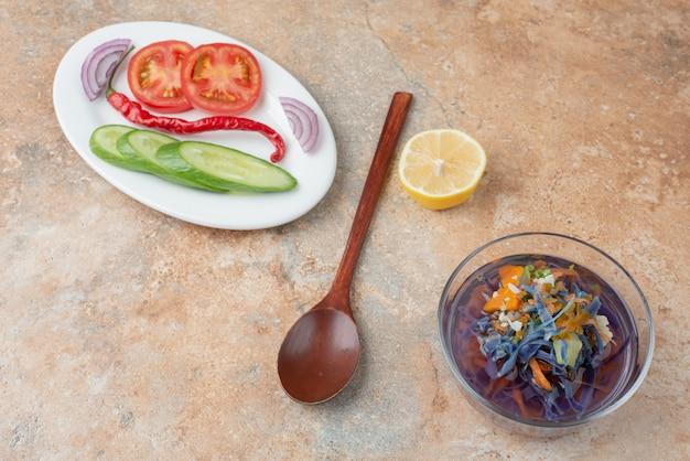 Délicieux thé avec concombre, tomate, tranche de citron et cuillère sur plaque blanche