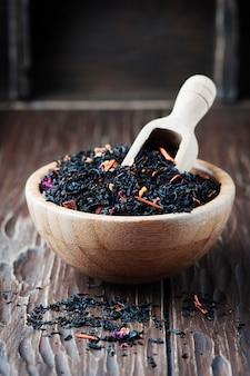 Délicieux thé noir aux pétales sur la table en bois