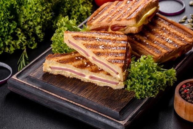 Délicieux toasts frais grillés avec du fromage et du jambon. sandwichs, collation rapide