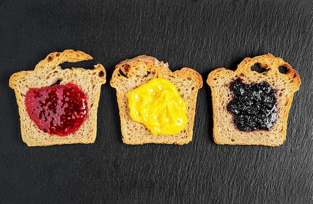 De délicieux toasts avec des sauces sucrées faites maison aux framboises, à la confiture de bleuets et au sabanion