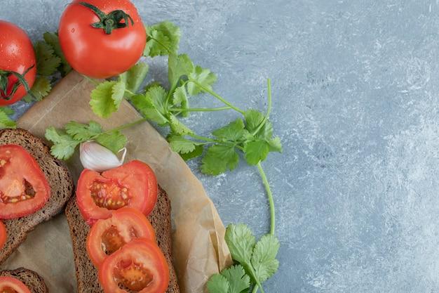 De délicieux toasts avec des tranches de tomate sur fond gris.