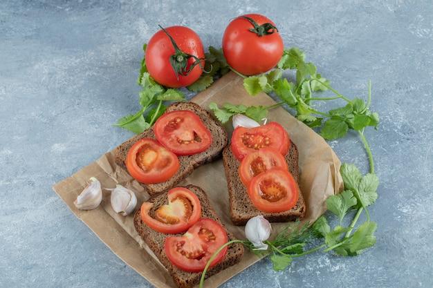 De délicieux toasts avec des tranches de tomate sur une surface grise.