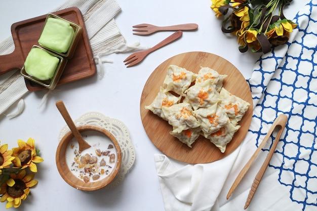 Délicieux tofu blanc avec des gâteaux verts et de la soupe kolak sur la plaque en bois du tableau blanc