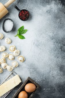 Délicieux tortellini crus avec de la farine et du basilic, sur fond gris, vue de dessus à plat,