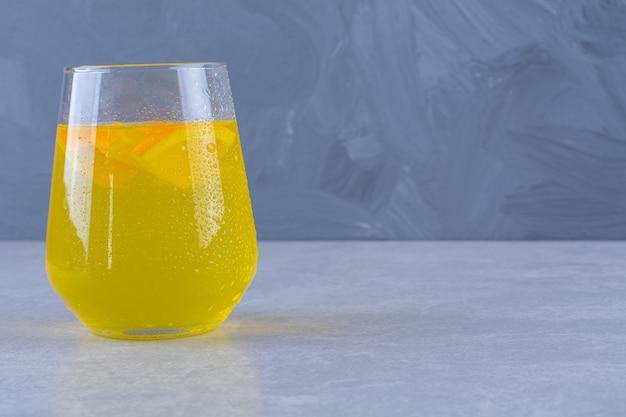 Délicieux un verre de jus d'orange sur une table en marbre.
