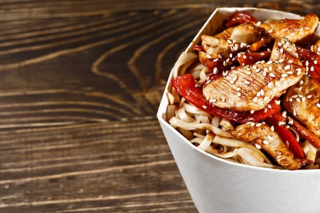 Délicieux wok noodles box container avec udon et poulet sur table en bois. restauration rapide à emporter chinoise et asiatique.