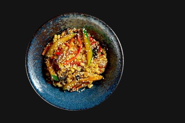 Délicieux wok de riz de rue avec légumes et cacahuètes dans une assiette. cuisine asiatique classique. livraison de nourriture. isolé sur fond noir
