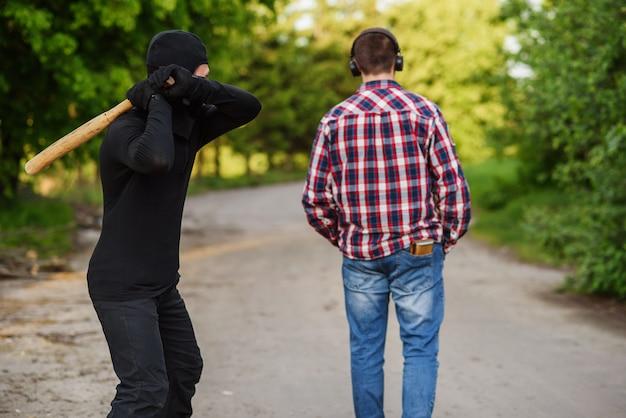 Un délinquant en tenue noire avec une batte de baseball à la main attaque un homme. vol à la tire dans la rue pendant la journée.