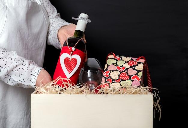 Deliver met une bouteille de vin avec un cœur rouge de la saint-valentin dans une boîte blanche avec un sac de fête et des verres à vin