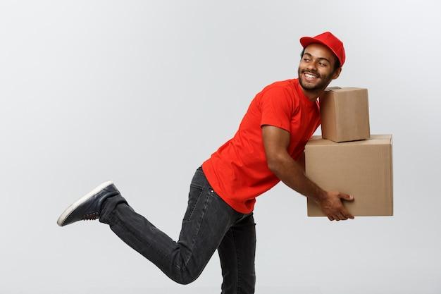 Delivery concept - handsome african american delivery man se précipite pour la livraison d'un paquet pour le client. isolé sur fond de studio gris. espace de copie.