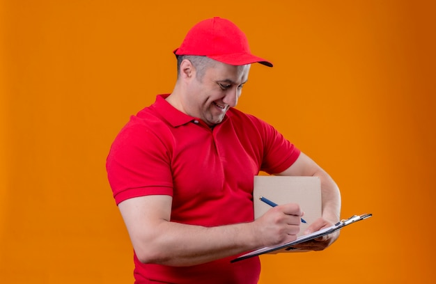 Delivery man wearing red uniform et cap holding box package et presse-papiers avec stylo souriant joyeusement sur mur orange isolé