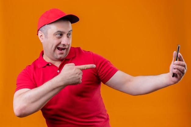Delivery man wearing red uniform et cap à joyful holding smartphone et pointant avec l'index vers lui souriant sur mur orange