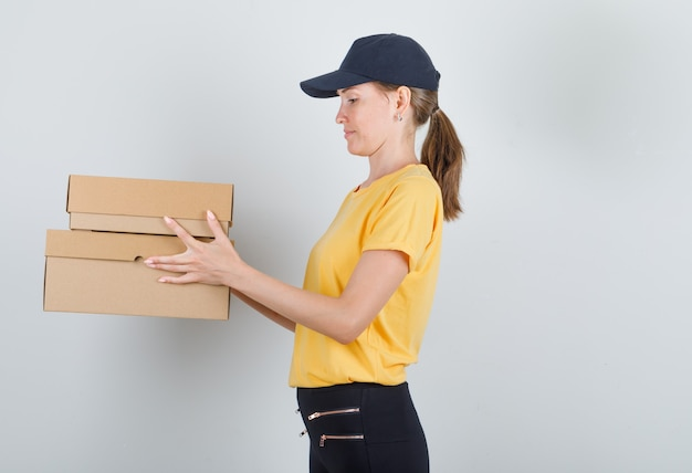 Delivery woman holding boîtes en carton en t-shirt, pantalon et casquette