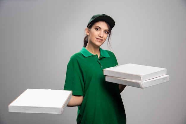 Delivery woman holding tas de pizzas