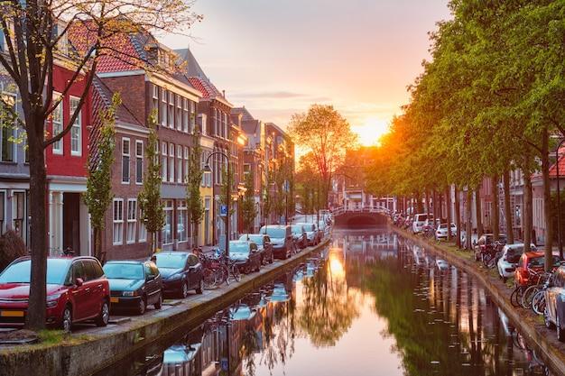 Delt canal avec vieilles maisons et voitures garées le long du coucher du soleil