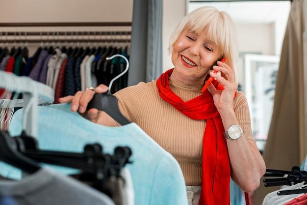 Demander un conseil. taille de l'adorable femme âgée tenant un cintre avec une robe tout en parlant avec son amie via téléphone mobile et en la consultant sur le shopping