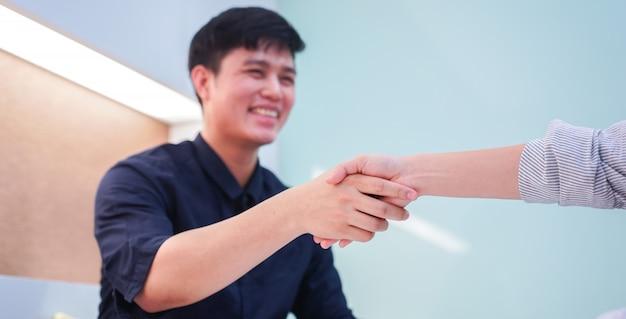 Demandeur asiatique main tremblante avec gestionnaire après contrat terminé dans une salle de conférence privée
