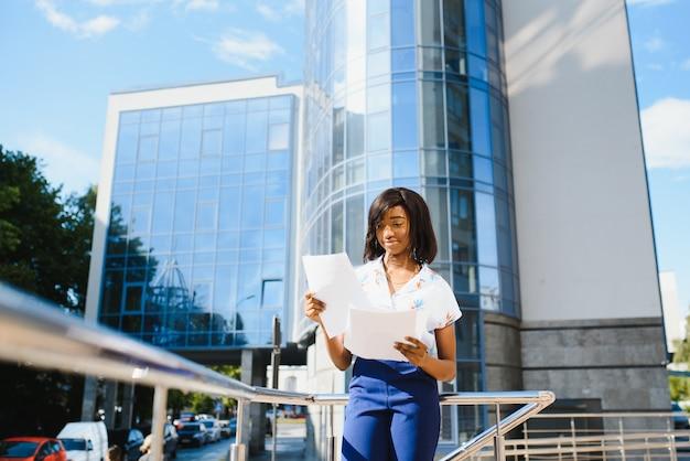 Demandeur d'emploi afro-américain en gardant un dossier avec cv dans ses mains debout contre un immeuble de bureaux