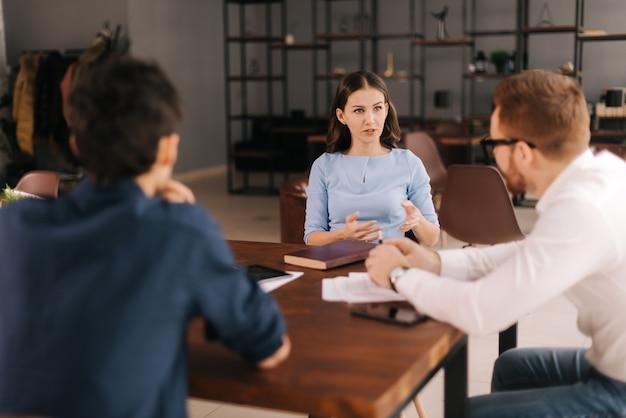 Demandeur d'emploi à l'entretien, la fille répond aux questions des intervieweurs