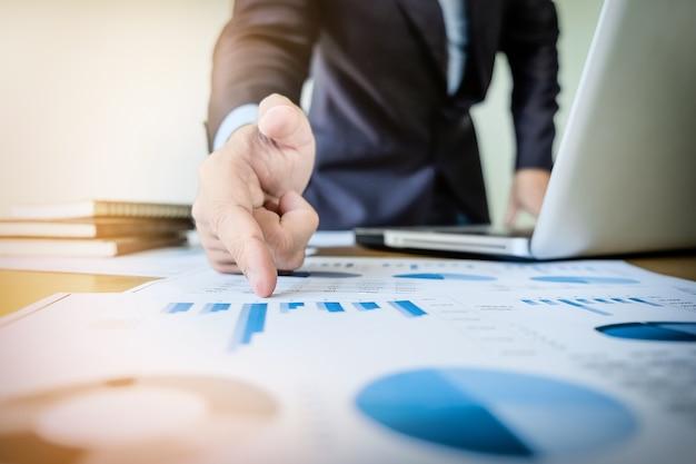 Démarrage du processus de travail. homme d'affaires travaillant avec un nouveau projet de financement au bureau avec des documents de tablette, de tablette et de graphique sur son bureau