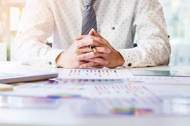 Démarrage du processus de travail. homme d'affaires travaillant à la table en bois avec un nouveau projet de financement. bloc-notes moderne sur la table. stylo tenant la main
