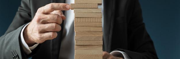Démarrage d'entreprise et idée - homme d'affaires faisant une pile de chevilles en bois vierges