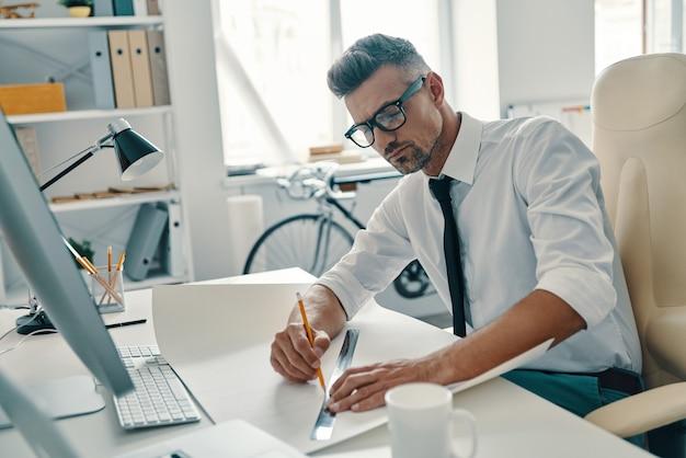 Démarrage d'un nouveau projet. beau jeune homme dessinant quelque chose alors qu'il était assis au bureau