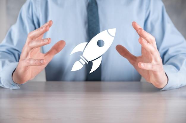 Démarrez le concept avec l'homme d'affaires détenant l'icône de fusée numérique abstraite fusée lance et monte en flèche.