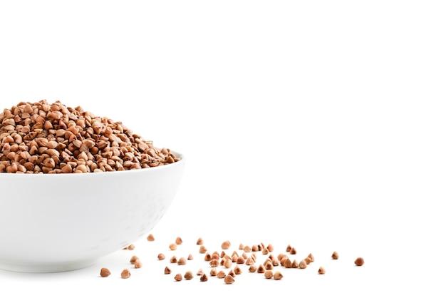 Une demi-assiette de sarrasin et de grains épars sur fond blanc, isolé. espace pour le texte