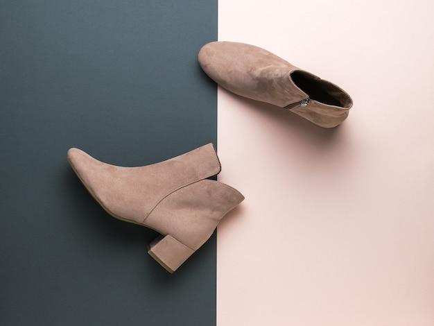 Demi-bottes femme en daim léger sur une surface noire et beige