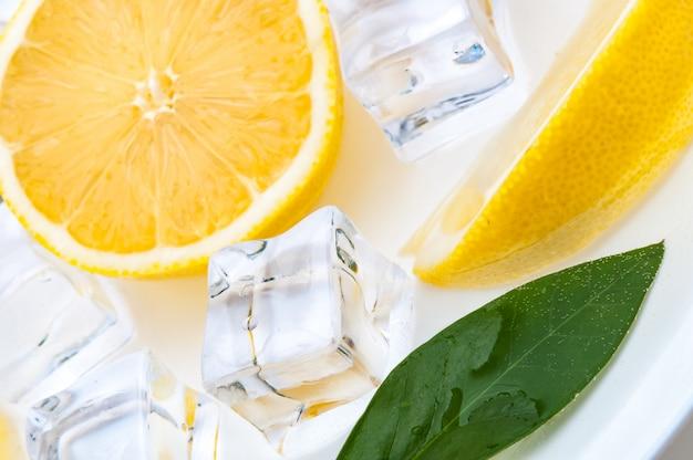 Un demi-citron lumineux et juteux avec une feuille verte et des cubes de glace rafraîchissante se bouchent
