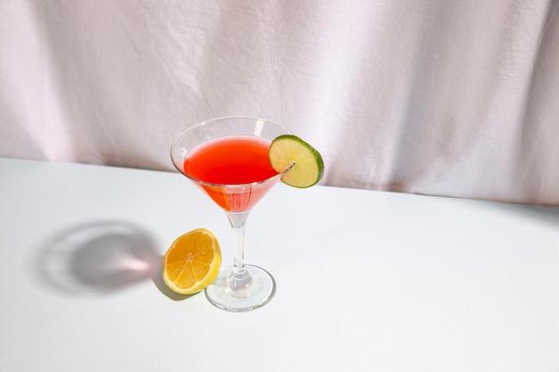 Demi citron vert avec boisson cocktail, garniture cocktail sur un bureau blanc