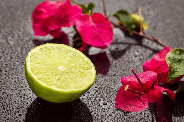 Demi citron vert frais et fleurs roses sur une surface humide. fermer